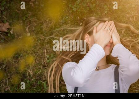 Close-up portrait of a happy young blond woman holding dreadlocks kneeling holding a yellow blossom in a spring garden - Stock Photo