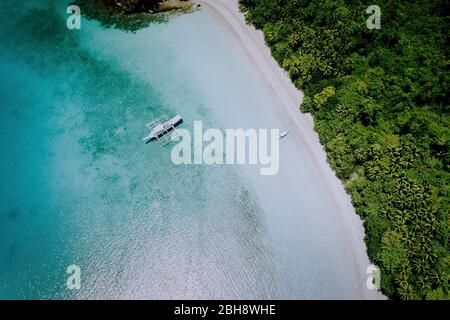 Aerial drone view of the beautiful paradise lagoon and white sand beach. Local boats on the surface. Summer exotic vacation concept.