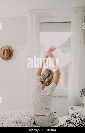 Woman sits in bed and stretches, back view