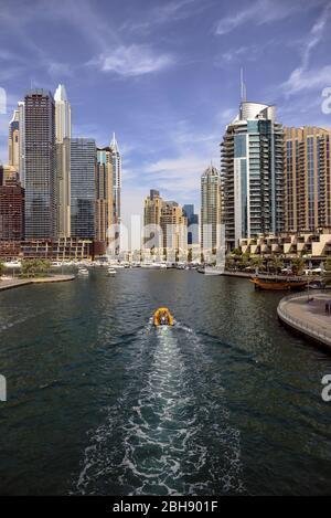 Blick auf ein Boot das gerade in den Hafen von Dubai Marina fährt, Uferpromenade und moderne Wolkenkratzer - Stock Photo