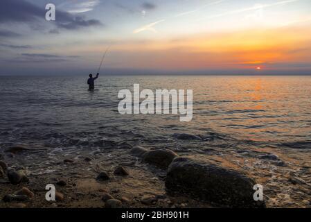 Silhouette eines Anglers in der Ostsee bei Sonnenuntergang - Stock Photo