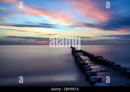 Buhnen in der Ostsee am Strand von Ahrenshoop bei Sonnenuntergang, durch Langzeitbelichtung die Wasseroberfläche der Ostsee eingefroren und Wolkenbewegung erkennbar - Stock Photo