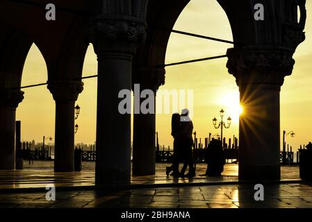 Silhouette of kissing romantic couple at Doge's Palace in Venice at sunrise on a wet winter morning - Stock Photo