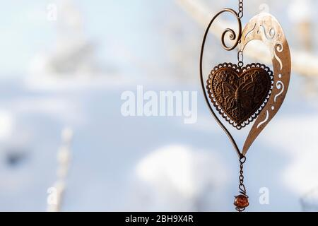 A decorative heart made of metal, rusted and with patina and a butterfly, in a snowy garden. - Stock Photo