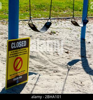 A sign warns visitors to a local community park that recreational amenities, such as this children's swing set, are closed due to COVID-19. - Stock Photo