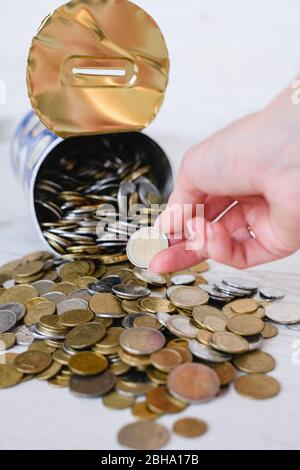 Savings of coins different currency, take last money from tin piggy bank during financial crisis, epidemy, inflation, pennies collection