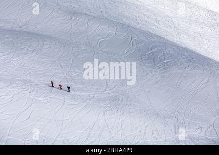 three ski mountaineers uphill on snow drawn by skiers' trails, Monte Alto (High Man), Hohe Tauern, Casies valley / Gsieser valley, South Tyrol, Italy - Stock Photo
