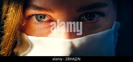 Eyes of a woman in a gauze mask looking at the camera close up. Preventive protection of your own health from viral infection. Coronavirus concept. - Stock Photo