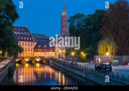 Tranquil canal night scene in La Petite France with the Spire of the Cathedral in the background and reflections of lights on the water, Strasbourg, Alsace, France a Unesco World Heritage Site - Stock Photo