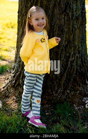 little girl leaning against the trunk of an old tree