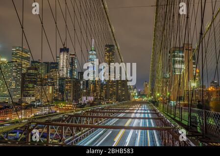 View over the Brooklyn Bridge with the illuminated silhouette of skyscrapers in downtown Manhattan for night long exposure - Stock Photo