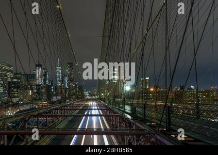 View over the Brooklyn Bridge At night to the illuminated skyscrapers in Manhattan - Stock Photo