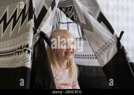 Portrait of happy 3-year-old toddler girl girl smiling while sitting in children play tent