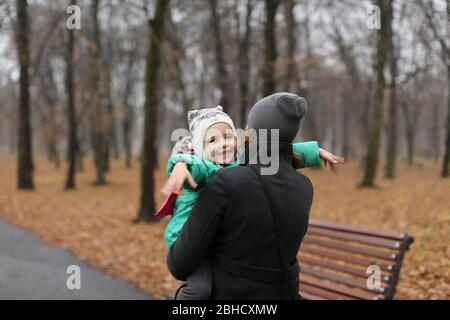 Mother carrying a toddler daughter in the autumn park