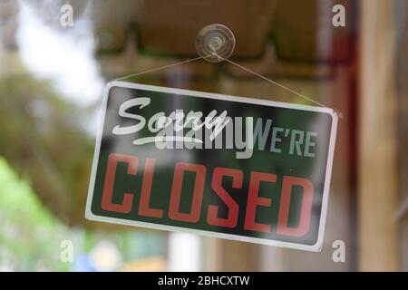 Close-up on an closed sign in the window of a shop saying 'Sorry, we're closed'. - Stock Photo