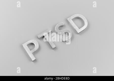 an abbreviation PTSD - post traumatic stress disorder - laid with silver metal letters on light gray flat surface