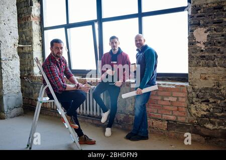 Three young engineers sitting by large window inside unfinished building, having coffee and relaxing at break in the middle of working day - Stock Photo
