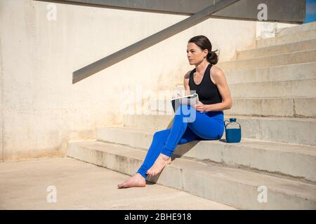 sporty woman sitting on steps outside writing in a notebook, journaling. - Stock Photo