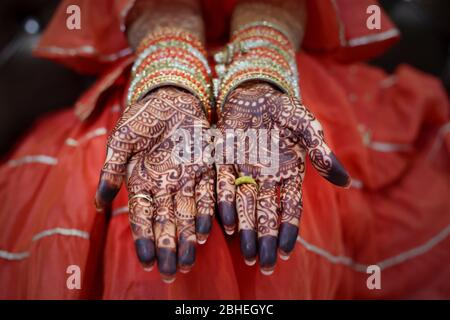 Indian bride showing hands with henna design on her wedding day - Stock Photo