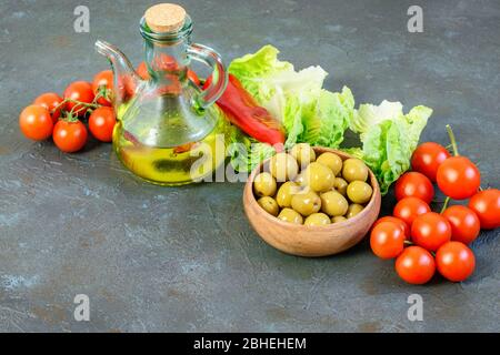 Light vegetables and olive oil bottle on the dark background. Balanced dietary products with vitamins and minerals. Healthy light lifestyle concept. - Stock Photo