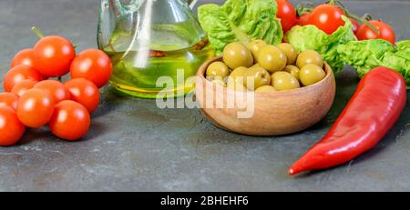 Dietary vegetables and healthy olive oil on the back background closeup. Healthy vegetables with vitamins and minerals. - Stock Photo