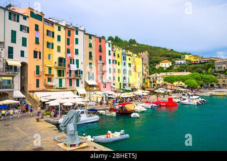 Portovenere, Italy, September 13, 2018: row of colorful multicolored buildings houses and restaurants of coastal town village and boats in harbor of National park Cinque Terre, La Spezia, Liguria - Stock Photo