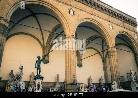 Florence, Italy, September 15, 2018: Statue of Perseus and Ratto delle Sabine in Loggia dei Lanzi on Piazza della Signoria square in historical city centre - Stock Photo