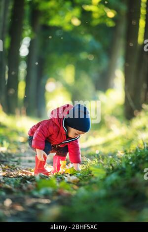 Little toddler boy in red rubber boots and red jacket in spring park. Lush green forest leaves on background