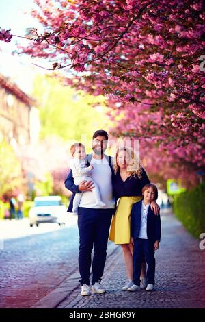 portrait of happy family on the walk along the blooming spring street - Stock Photo