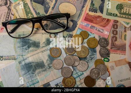 Eye glasses with World international banknotes vary countries background. US Dollar, Chinese yuan, Japanese yen, Euro, Korea won, Thai baht. Concept o