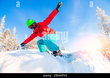 Active man snowboarder riding on slope during sunny day in mountains. Dust snow forest - Stock Photo
