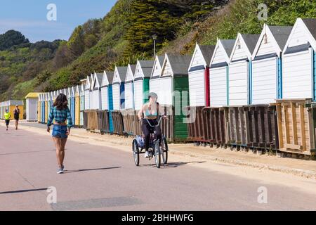 Bournemouth, Dorset UK. 26th April 2020. UK weather: lovely warm sunny day as temperatures rise at Bournemouth beaches on the South Coast as people take their permitted exercise, most adhering to the Coronavirus guidelines. Beaches are practically deserted as police and council workers patrol the area.  Young woman cycling along promenade on tricycle past beach huts - riding bike bicycle trike tricycle cyclist cyclists. Credit: Carolyn Jenkins/Alamy Live News - Stock Photo