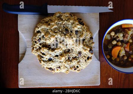 Fresh baked Irish soda bread (with raisins) on a wooden chopping board, next to a blue bowl of bean and vegetable stew. That was a fine supper!