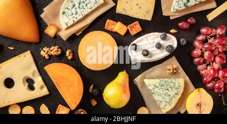 Cheese flat lay panorama. Many different cheeses, shot from above on a dark background - Stock Photo