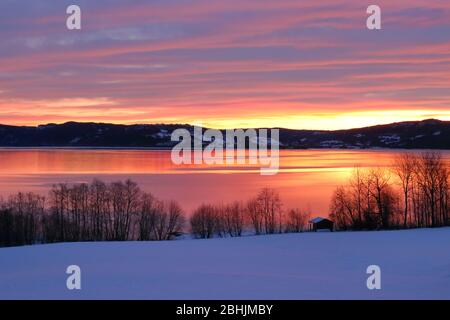 Scenic view of an amazing winter sunset reflected in the calm Selbusjøen lake, Selbustrand, Norway - Stock Photo