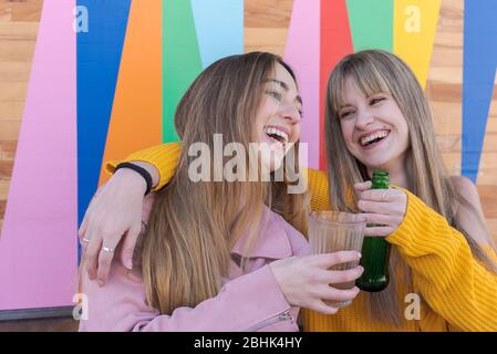 Two happy young Caucasian women toast with drink on the multicolored wall of a city bar - Stock Photo