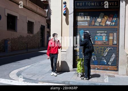Dos personas con mascarillas charlan delante de tiendas cerradas por la cuarentena, 25 abril 2020, Gracia, Barcelona, España. - Stock Photo