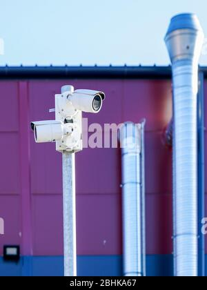 a pillar with two surveillance cameras on the back of the factory - Stock Photo