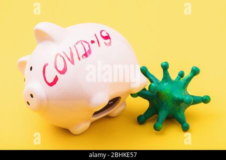 Piggy bank with the inscription and toy coronavirus on a yellow background. Concept on the lack of money during quarantine due to the covid-19 pandemi - Stock Photo