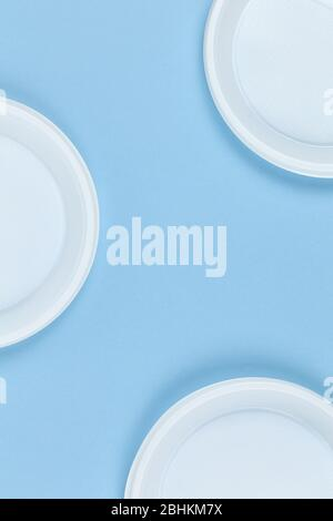 Disposable plastic dishes, plates, blue background, copy space. For social media. Frame of objects. Environmental pollution, rejection of non-recyclab - Stock Photo
