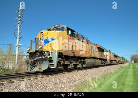 Geneva, Illinois, USA. Four locomotives leading a freight train of stack or container cars on a westward journey from Chicago. The multi-track line li - Stock Photo