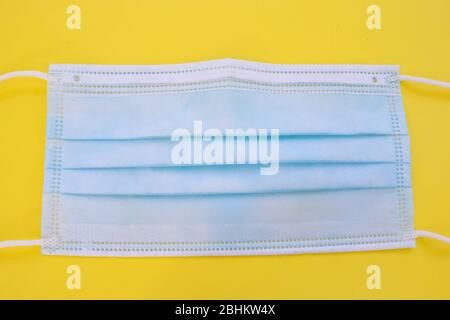 Surgical mask with rubber ear straps. Typical 3-ply surgical mask, against covid. Procedure mask from bacteria. Protection concept. - Stock Photo