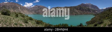 Panorama of the blue green Iskanderkul lake in Tadzjikistan with high snowy mountains. - Stock Photo
