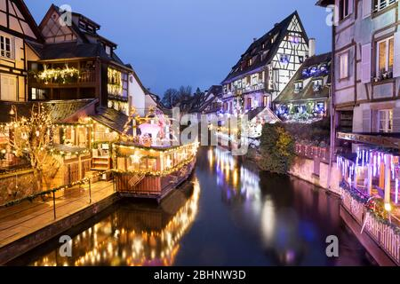 View of old half-timbered restaurants and hotels along La Lauch at night in the Little Venice area, Colmar, Alsace, France, Europe - Stock Photo