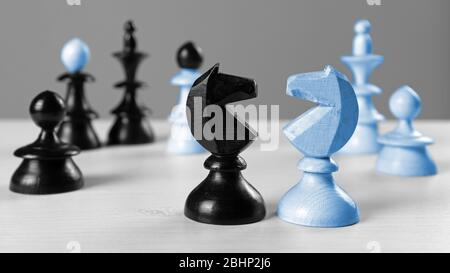 Two knights facing each other on a white wooden table, with other chess pieces in the background - Stock Photo