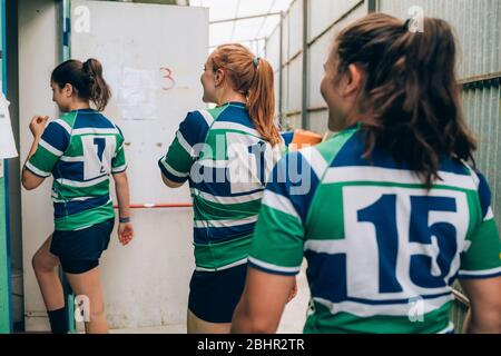 Rear view of three women wearing blue, white and green rugby walking through a door into a building. - Stock Photo