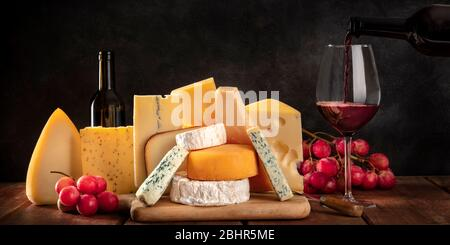 Cheese panorama, mvarious cheeses with grapes and pouring wine, a side view on a dark background with a place for text - Stock Photo