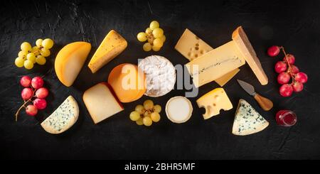 Cheese panorama, various cheeses, shot from above on a dark background with grapes - Stock Photo
