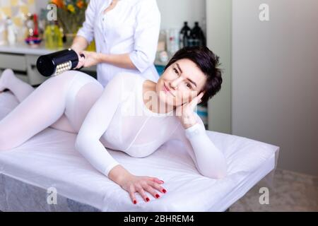 Lymphatic drainage massage LPG or R-sleek apparatus process. Woman in white suit getting anti cellulite massage in a beauty salon. Skin and body care. - Stock Photo