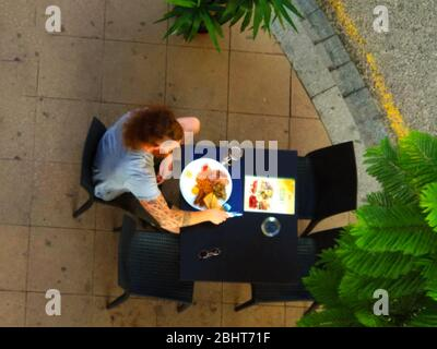 English breakfast with eggs and beans of a boy at the table seen from above in summer - Stock Photo
